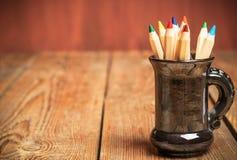 Crayons dans une tasse sur une table en bois Photo stock