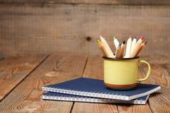 Crayons dans une tasse sur une table en bois Images libres de droits
