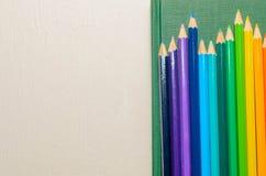 Crayons de couleur, carnet sur le fond blanc Photos stock