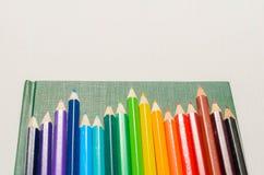 Crayons de couleur, carnet sur le fond blanc Photographie stock