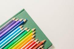 Crayons de couleur, carnet sur le fond blanc Photo libre de droits