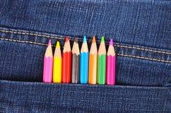 Crayons de couleur dans la poche de blues-jean Photographie stock