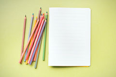 Crayons de couleur et cahier vide Photo stock