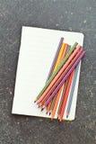 Crayons de couleur et cahier vide Images libres de droits