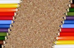 Crayons de couleur sur le fond de liège Image libre de droits