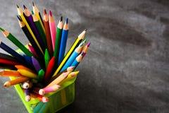 Crayons de couleur sur le fond de tableau noir Photographie stock