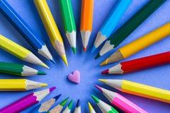 Crayons de couleur sur le fond de papier pourpre Image stock