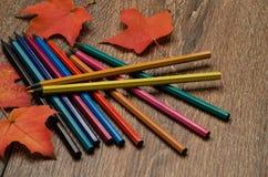 Crayons de différentes couleurs et feuilles d'automne sur la table Image libre de droits