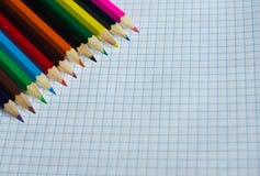 Crayons de différentes couleurs sur un carnet ouvert Photographie stock