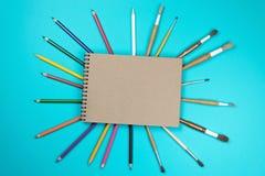Crayons de inscription colorés de stylos d'accessoires d'outils de papeterie, papier d'emballage d'isolement sur le fond bleu De  photographie stock