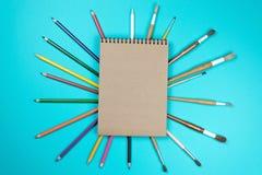 Crayons de inscription colorés de stylos d'accessoires d'outils de papeterie, papier d'emballage d'isolement sur le fond bleu De  images stock