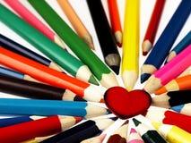 Crayons en bois colorés et coeur rouge Images libres de droits