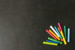 Crayons en pastel lumineux se trouvant sur un conseil pédagogique noir ` S d'enfants Photo stock