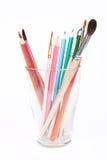 Crayons et balais dans une cuvette en verre Images stock