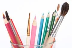 Crayons et balais dans une cuvette en verre Photos stock