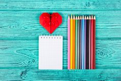 Crayons et bloc-notes de couleur Origami rouge de coeur Photo stock