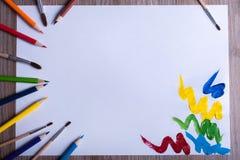 Crayons et brosses colorés sur le livre blanc Photos libres de droits