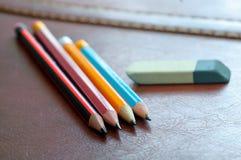 Crayons et gomme Accessoire sur le fond brun naturel selec Photos stock