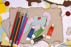 Crayons et peintures sur le vieux papier photos stock