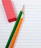 Crayons et une gomme à effacer sur le papier de cahier Photos stock