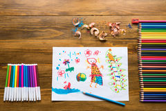 Crayons, felt-tip pens and a child`s drawing. On a wooden table stock image