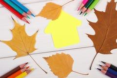 Crayons, forme du bâtiment et feuilles automnales sur les conseils blancs Image libre de droits