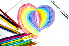 Crayons and heart on notebook. Rainbow colored heart with crayons on notebook Royalty Free Stock Photography