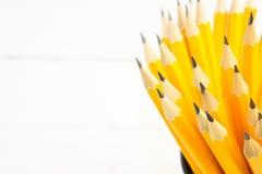 crayons jaunes en verre noir sur un fond blanc Images stock