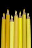 7 crayons jaunes - fond noir Photos stock
