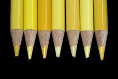 7 crayons jaunes - fond noir Image libre de droits