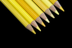 7 crayons jaunes - fond noir Photographie stock
