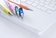 Crayons lecteurs colorés sur le clavier blanc d'ordinateur portatif Photographie stock libre de droits