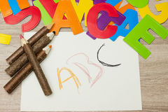 Crayons and letters. Some crayons are along with many letters on a sheet of paper with ABC Stock Photo