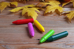 Crayons and maple leaves Royalty Free Stock Photography