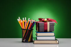Crayons, markers, books and a present Royalty Free Stock Photos