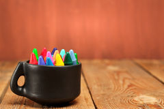 Crayons in a mug on a wooden table Royalty Free Stock Image