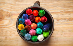 Crayons in a mug on a wooden table Stock Images