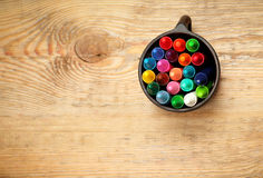 Crayons in a mug on a wooden table Stock Photography