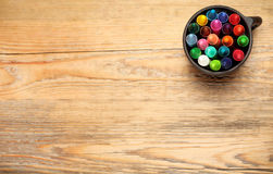 Crayons in a mug on a wooden table Stock Photos