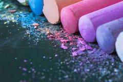 Crayons multicolores, en pastel Vert, jaune, rose, pourpre, bleu Pastels peints Craie renversée sur un conseil vert Images stock