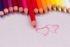 Crayons multicolores sur la texture de papier en pastel beige de grunge de céréale secondaire Photographie stock