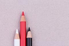 Crayons multicolores sur la texture de papier en pastel beige de grunge de céréale secondaire Photos stock