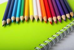 Crayons multicolores sur le cahier vert Images stock