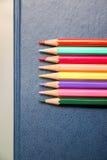 Crayons multicolores sur un fond bleu Images stock