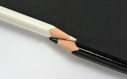 Crayons noirs et blancs sur le même fond de papier Photo libre de droits