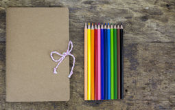 Crayons and notebooks Stock Images