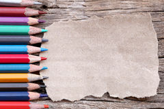 Crayons ou crayons colorés et carton brun sur le vieux flo en bois Images stock