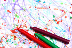 Crayons on paper far. Multicolored crayons on a multicolored background Royalty Free Stock Image