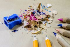 Crayons and pencil sharpener on a wooden office table. Crayons w Royalty Free Stock Image
