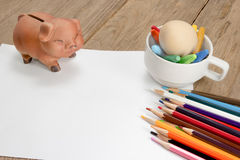 Crayons and piggy bank on a sheet of paper Stock Photography